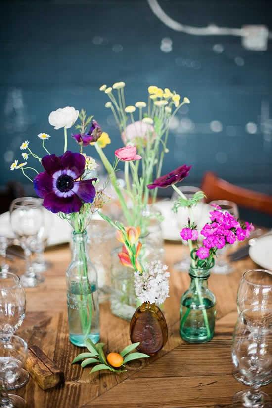 Decoração com garrafinhas e arranjos de flores